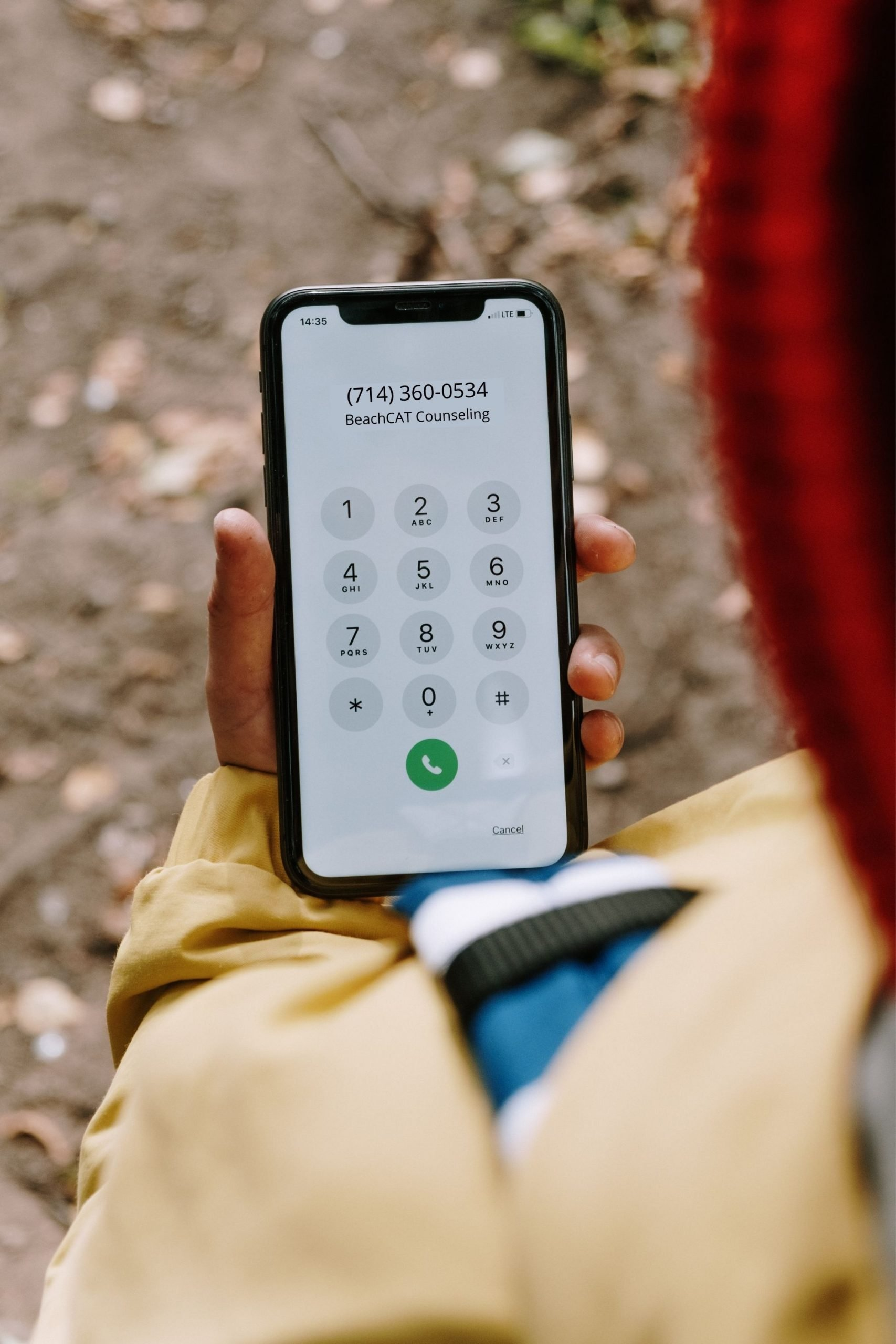 """A person who is looking for a mental health therapist is looking at their phone and is about to make a call. The phone screen shows the name """"BeachCAT Counseling"""" and the phone number, """"714-360-0534."""""""